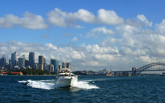 motor yacht speeding around Sydney Harbor with the city skyline and Sydney Harbour Bridge in the background