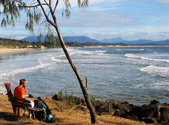 visitor strumming a guitar on a bench overlooking the beach, Byron Bay