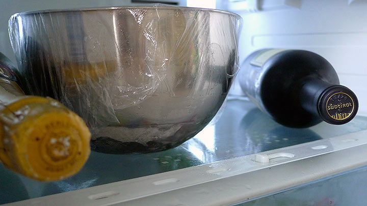 bowl covered with plastic wrap in the refrigerator