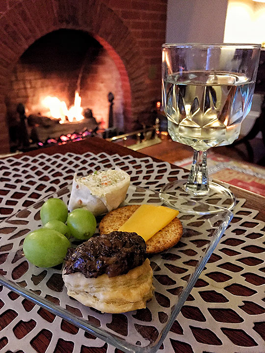 appetizers and fireplace in a Cheshire Cat Inn room