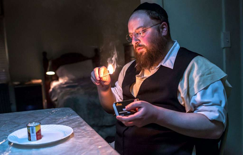Menashe Lustig lights a memorial candle for his deceased wife