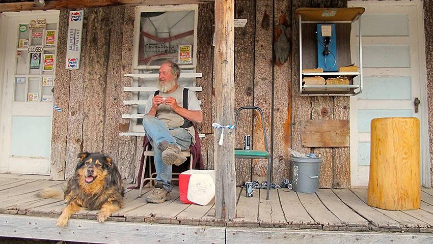man and his dog at a storefront porch