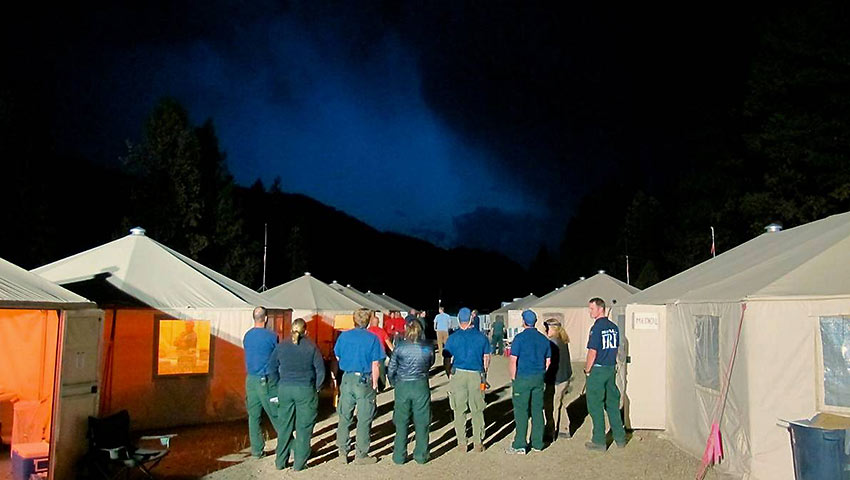 firefighters observe a thunderstorm from their camp