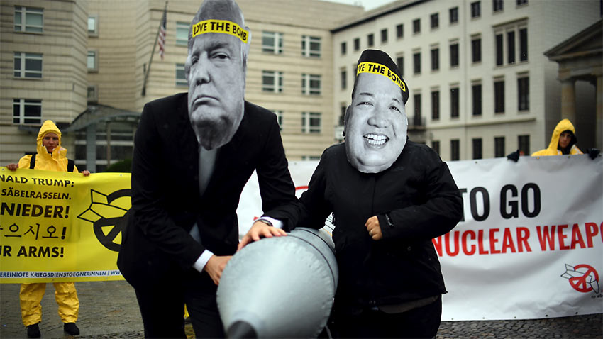 protesters with Donald Trump and Kim Jong Un face masks