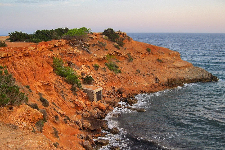 fisherman's shacks below red cliffs on the water's edge