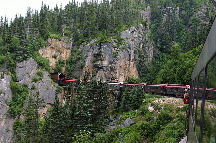 a train emerges from a tunnel on the White Pass and Yukon Route