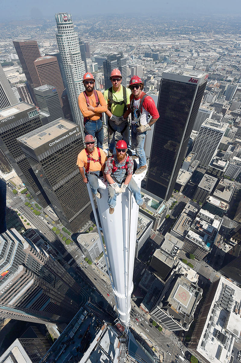 workers pose on top of the 300-ft-tall spire atop the Wilshire Grand Center