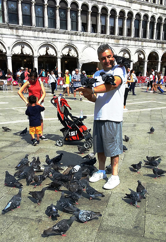 man feeding pigeons at the Piazza San Marco