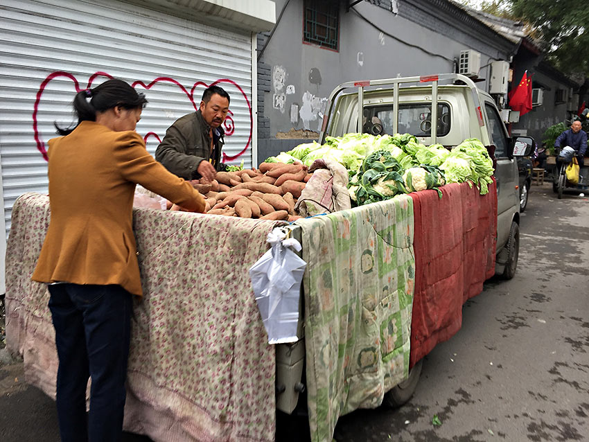 sweet potatoes, cauliflower, and lettuce driven directly from a farm and sold from the back of a truck in one of Beijing's ancient rundown hutongs or connecting courtyards