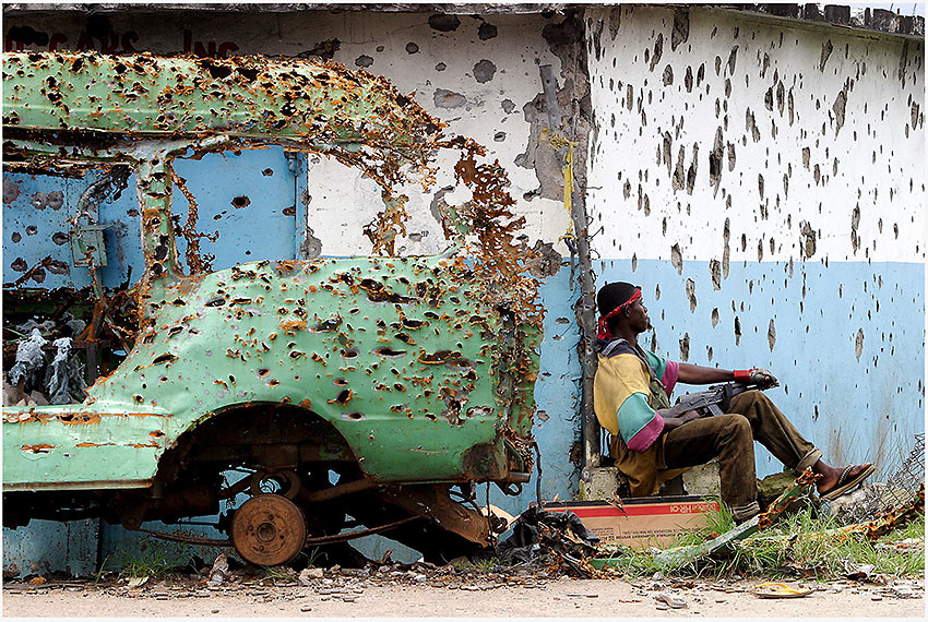 shrapnel-riddled vehicle and building in Liberia