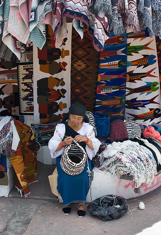 a weaver and her products at Otavalo's Craft Market, Plaza de Ponchos, Quito