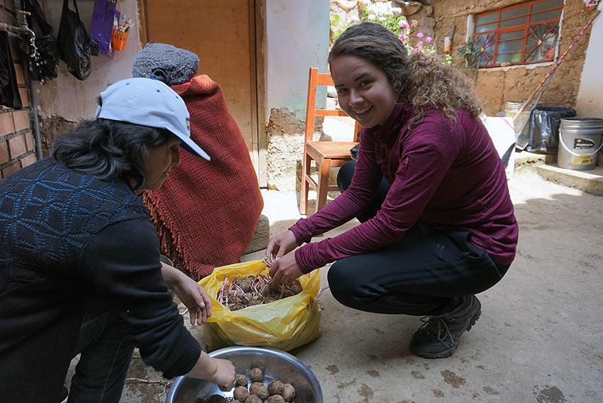 author's sister helping locals peel potatoes