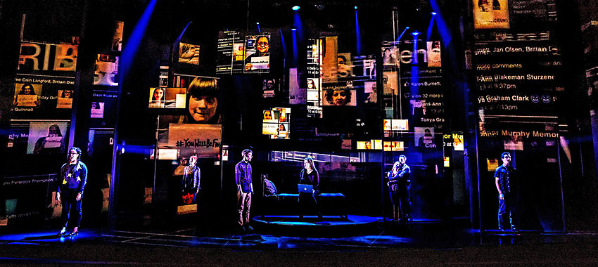 "the Company of ""Dear Evan Hansen"" with Peter Nigrini's projection design of internet chatter in the background"