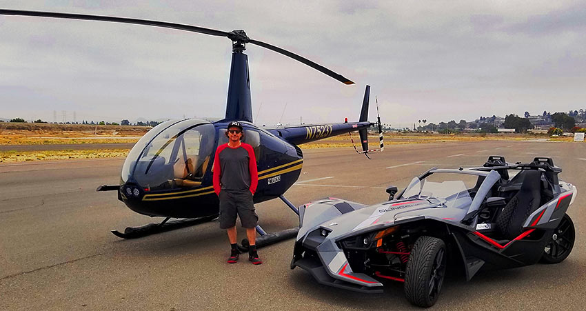 writer with helicopter and Polaris Slingshot at Oceanside