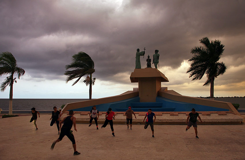 locals exercising on Campeche's malecón with the Gulf of Mexico in the background