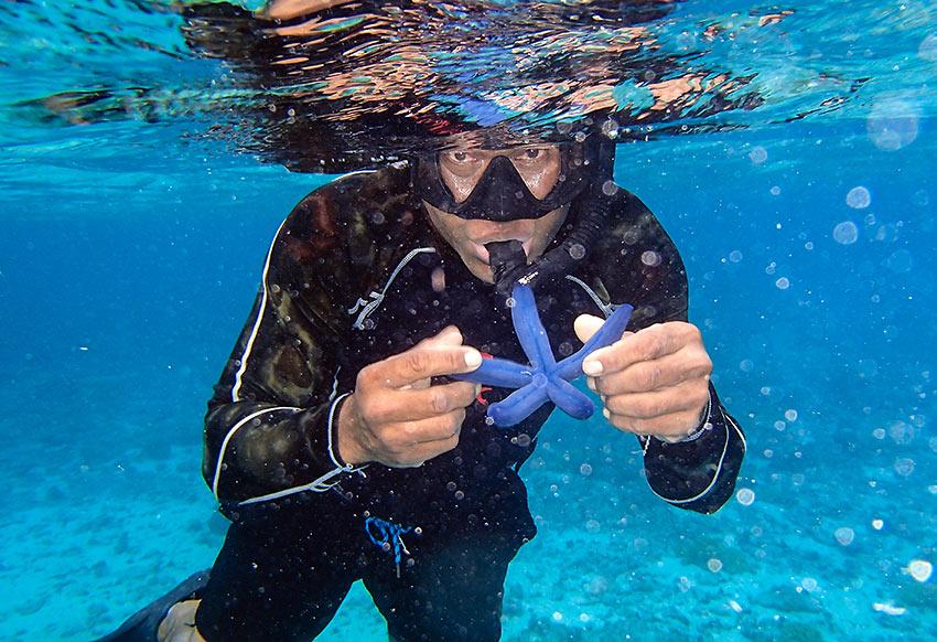 snorkling guide Niu Lebaivalu with blue starfish at Honeymoon Island