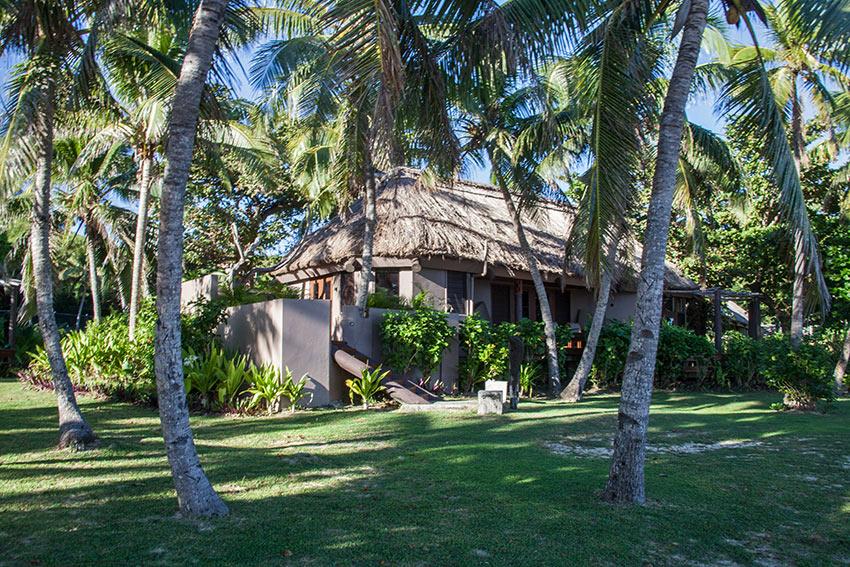 shade palms, green lawns and cottage at Yasawa Island Resort