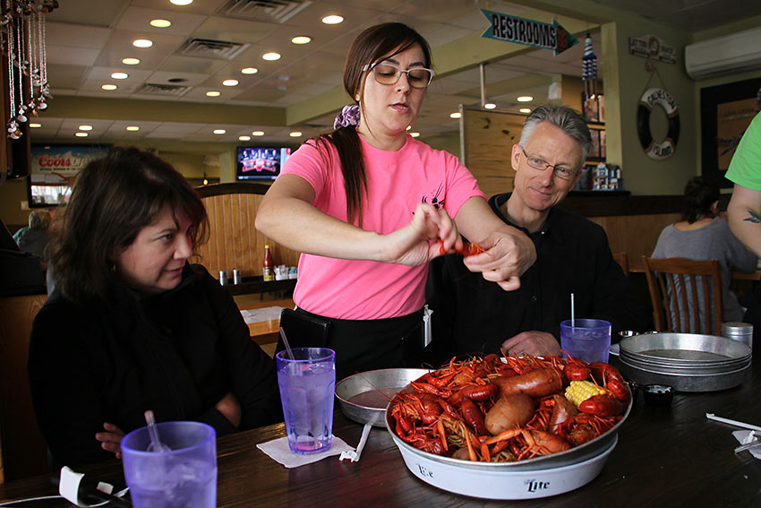 Galveston waitress demonstrates the correct etiquette for eating a crawfish boil