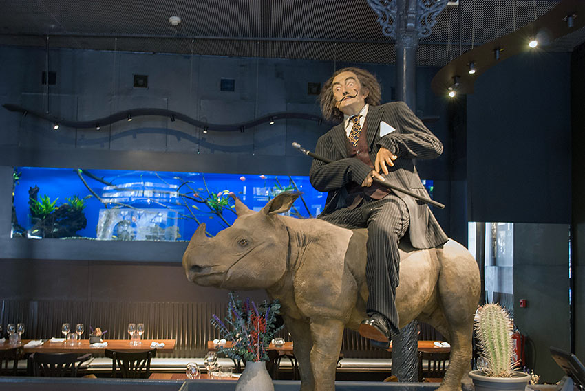 a large print of Dali riding a baby rhinoceros