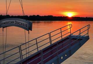 sunset on Mississippi River framed by a gangway on the American Duchess