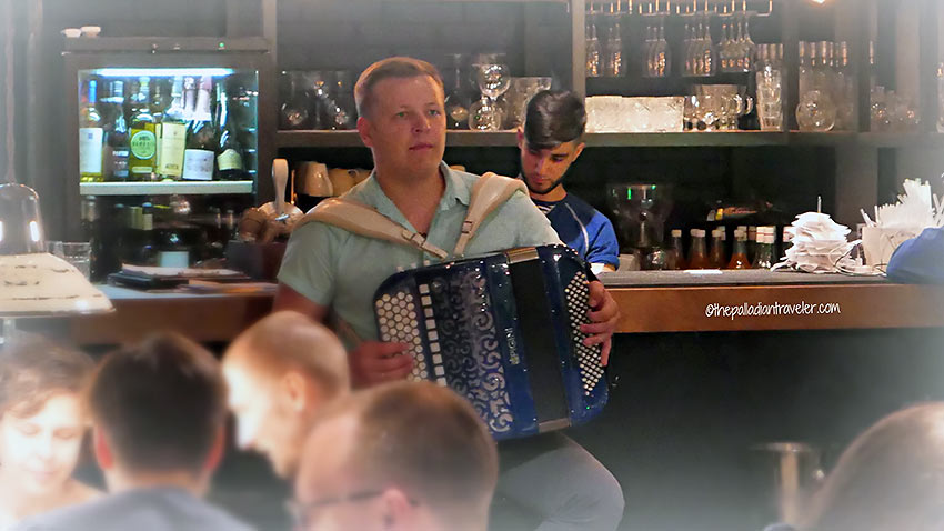 young musician playing traditional tunes on a squeeze box at the Odessa Mama