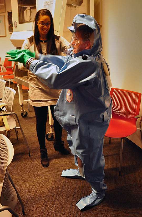putting on a biosafety suit at the David J. Sencer CDC Museum
