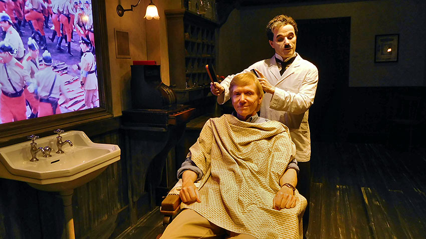 Charlie Chaplin barber recreator giving haircut at Chaplin's World