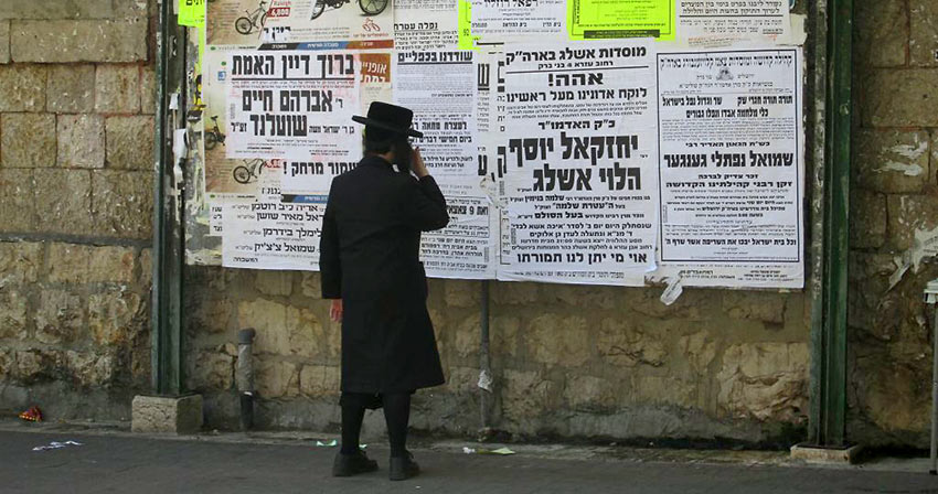 young Hasidic man reading posted news
