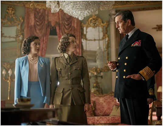 Princess Margaret Rose (Bel Powley) and Elizabeth (Sarah Gadon) receive instructions from their father, King George VI