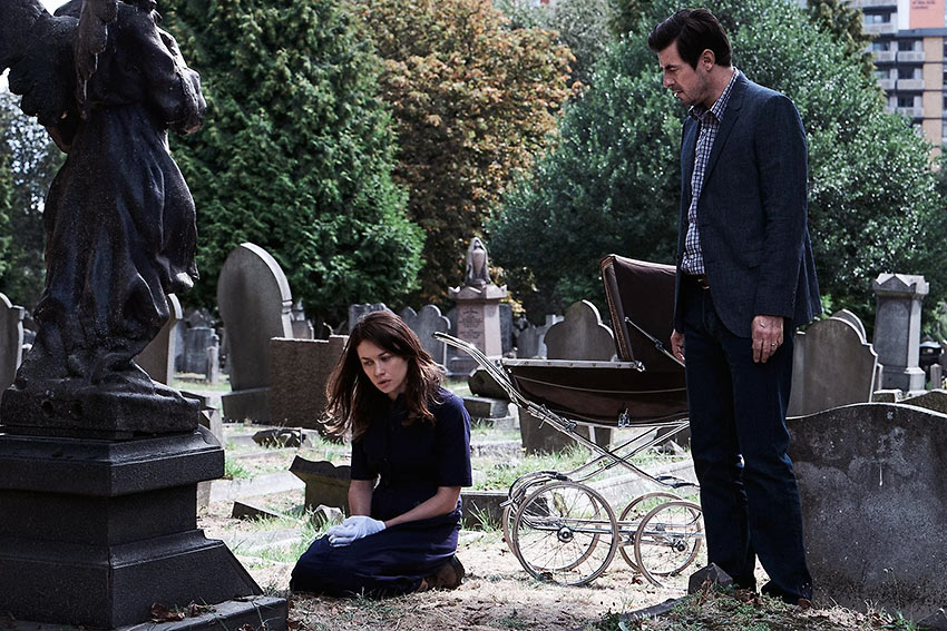 With a baby carriage looming in the background, Rosalind (Olga Kurylenko) with her husband Will (Claes Bang) visit a mystery grave