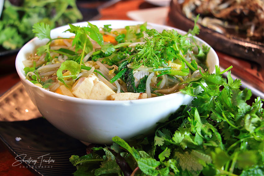 green vegetables and a bowl of pho