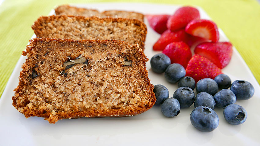 banana bread with walnuts and a side of berries