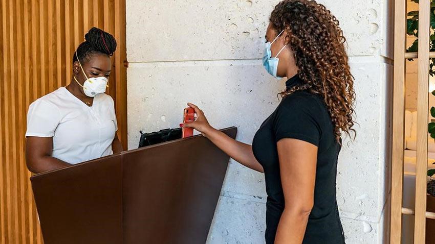woman has her Covid health app checked at the Grand Hyatt Baha Mar