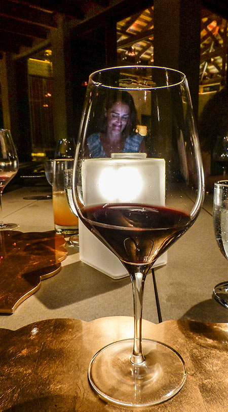 Villa Manager Jenifer Cowles, at dinner, seen through a glass of wine